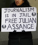A protester holds a banner outside Westminster Magistrates Court in London, where Julian Assange is due to appear, Monday, Jan. 13, 2020. Protesters will be insisting that Assange should not be extradited to the US for his reporting of the Iraq and Afghanistan war. They insist he will not face a fair trial in the United States where the charges against him could result in imprisonment for 175 years. Assange will be transported from Belmarsh high-security prison. (AP Photo/Kirsty Wigglesworth)