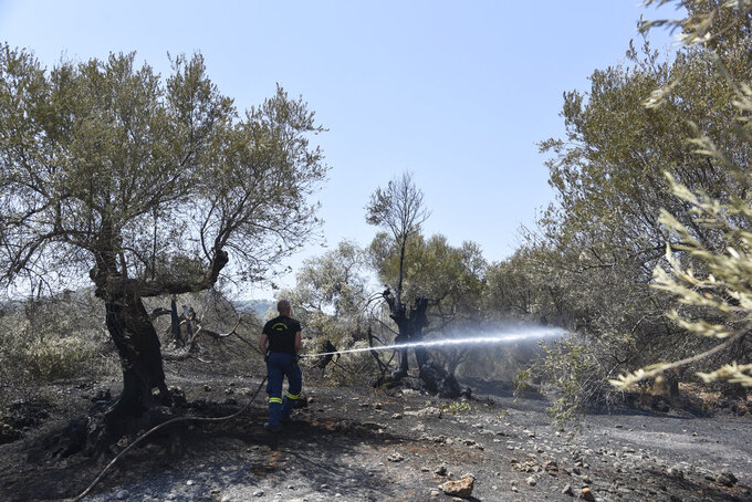 A firefighter operates near Ziria village, east of Patras, Greece, Sunday, Aug. 1, 2021. A wildfire that broke out Saturday in western Greece forced the evacuation of four villages and people on a beach by the Fire Service, the Coast Guard and private boats, authorities said. (AP Photo/Andreas Alexopoulos)