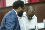 Attorney Norman Williams, left, speaks to James Currie during his arraignment in Manhattan criminal court, Friday, Aug. 10, 2018, in New York. Currie is accused of throwing the lifeless body of his son, Mason Saldana, into the East River near the Brooklyn Bridge last Sunday. A tourist spotted the child's diaper-clad body and waded into the water to retrieve it. (AP Photo/Mary Altaffer)