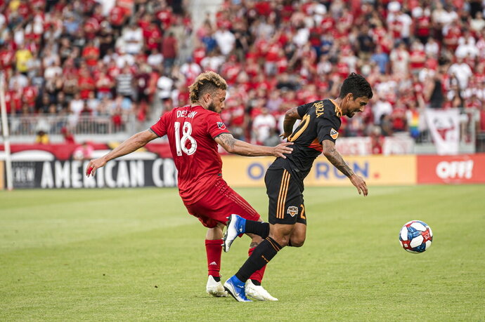 Toronto FC midfielder Nick DeLeon (18) defends against Houston Dynamo defender A. J. DeLaGarza (20) during the first half of an MLS soccer game, Saturday, July 20, 2019 in Toronto. (Christopher Katsarov/The Canadian Press via AP)