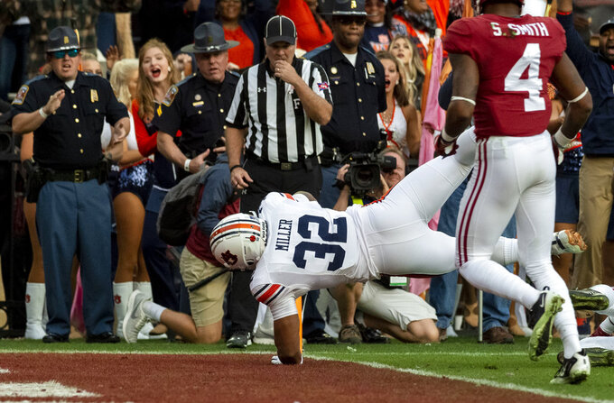 Auburn running back Malik Miller (32) runs a pass reception from Auburn wide receiver Ryan Davis (23) in for a touchdown during the first half of an NCAA college football game, Saturday, Nov. 24, 2018, in Tuscaloosa, Ala. (AP Photo/Vasha Hunt)