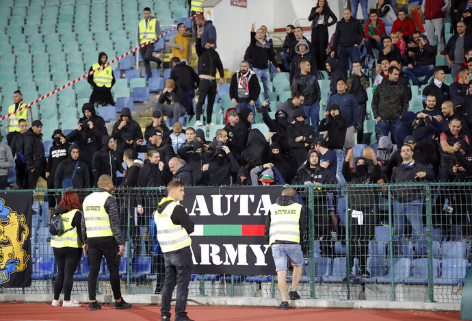 EDS NOTE OBSCENE GESTURES - Bulgarian fans gesture as they stand in the stadium to watch the Euro 2020 group A qualifying soccer match between Bulgaria and England, at the Vasil Levski national stadium, in Sofia, Bulgaria, Monday, Oct. 14, 2019. (AP Photo/Vadim Ghirda)