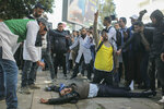 An injured protesting teacher is tended to by fellow protesters after security forces used water cannons and batons to disperse a demonstration in Rabat, Morocco, Wednesday, Feb. 20, 2019. The thousands of protesters, many wearing white teachers' robes, came from around Morocco to Rabat to seek salary raises and promotions and protest the limited opportunities for low-ranking teachers, who earn an average of 400 euros ($454) a month. (AP Photo/Mosa'ab Elshamy)