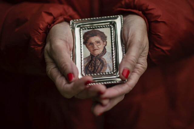 In this Thursday, May 14, 2020 photo, Teresa Navarro shows a picture of her mother Concepcion Rosillos, 97, in Madrid, Spain. Concepcion Rosillos was one of the residents at the Usera Center for the Elderly, who died during the coronavirus outbreak in Spain.  More than 19,000 coronavirus deaths in Spain's nursing homes have prompted a re-examination of a system. (AP Photo/Bernat Armangue)