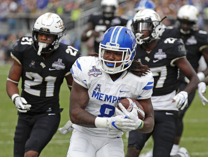 Memphis running back Darrell Henderson, center, runs past Central Florida defensive backs Rashard Causey (21) and  Richie Grant, right, for a 12-yard touchdown run during the first half of the American Athletic Conference championship NCAA college football game, Saturday, Dec. 1, 2018, in Orlando, Fla. (AP Photo/John Raoux)