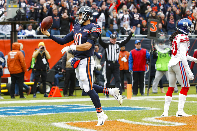 Chicago Bears quarterback Mitchell Trubisky (10) celebrates a touchdown behind New York Giants cornerback Janoris Jenkins (20) during the second half of an NFL football game in Chicago, Sunday, Nov. 24, 2019. (AP Photo/Charles Rex Arbogast)