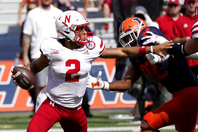 Nebraska quarterback Adrian Martinez eludes Illinois linebacker Isaiah Gay during the second half of an NCAA college football game Saturday, Aug. 28, 2021, in Champaign, Ill. Illinois won 30-22. (AP Photo/Charles Rex Arbogast)