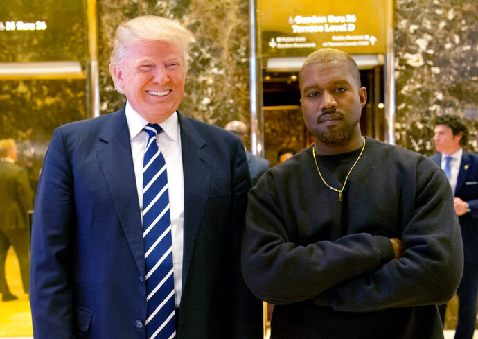 "FILE - In this Dec. 13, 2016, file photo, then-President-elect Donald Trump and Kanye West pose for a picture in the lobby of Trump Tower in New York. Trump is tweeting his thanks to rap superstar Kanye West for his recent online support. Trump wrote, ""Thank you Kanye, very cool!"" in response to the tweets from West, who called the president ""my brother."" West tweeted a number of times Wednesday expressing his admiration for Trump, saying they both share ""dragon energy."" The rap star also posted a photo of himself wearing Trump's campaign ""Make America Great Again"" hat. (AP Photo/Seth Wenig, File)"