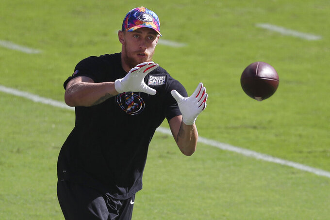 """FILE - San Francisco 49ers tight end George Kittle wears Crucial Catch clothing as he warms up before an NFL football game against the Miami Dolphins in Santa Clara, Calif., in this Sunday, Oct. 11, 2020, file photo. The NFL is launching its """"Crucial Catch"""" initiative this month, and it is concentrating on getting screened to catch cancer early when it may be easier to treat.  The COVID-19 pandemic has had a devastating impact on screening, with some cancer screenings declining by 90%. So the league and the American Cancer Society are allocating resources dedicated to safely restarting cancer screenings in communities with the most need. (AP Photo/Jed Jacobsohn, File)"""