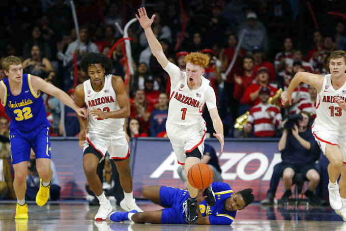 Arizona guard Nico Mannion (1) is fouled by South Dakota State guard Brandon Key (0), center bottom, in the second half during an NCAA college basketball game, Thursday, Nov. 21, 2019, in Tucson, Ariz. (AP Photo/Rick Scuteri)