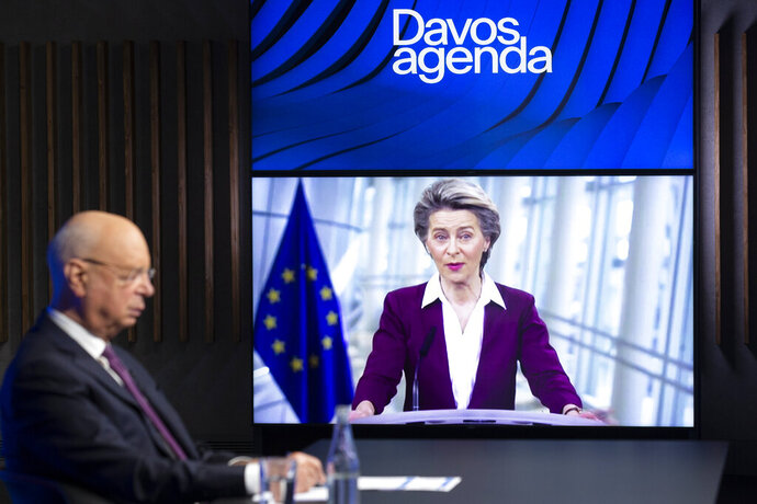 German Klaus Schwab, left, Founder and Executive Chairman of the World Economic Forum, WEF, listens to European Commission President Ursula von der Leyen, displayed on a video screen, during a conference at the Davos Agenda in Cologny near Geneva, Switzerland, Tuesday, Jan. 26, 2021. The Davos Agenda from Jan. 25 to Jan. 29, 2021 is an online edition due to the coronavirus disease (COVID-19) outbreak. (Salvatore Di Nolfi/Keystone via AP)