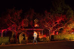 A Pacific Gas & Electric worker passes a home on Merrill Dr. in Moraga, Calif., as firefighters work to contain a wildfire burning behind it on Thursday, Oct. 10, 2019. Police ordered evacuations as the fast-moving wildfire spread in the hills of the San Francisco Bay Area community. The area is without power after Pacific Gas & Electric preemptively cut service to more than half a million customers hoping to prevent wildfires during dry, windy conditions. (AP Photo/Noah Berger)