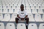 In this Saturday, May 4, 2019, Francis Kalombo from Congo poses for a photograph at the Municipality stadium of Mytilene, on the northeastern Aegean island of Lesbos, Greece. A 10-minute walk from Europe's largest refugee camp sits a nondescript yet remarkable soccer field. It's a place where residents of the Moria camp on the Greek island of Lesbos can briefly forget about their tiny container-homes and crowded tents and instead worry about corner kicks and throw-ins. And it's the place where 15-year-old Francis Kalombo became the first refugee to sign for a professional Greek soccer club. (AP Photo/Thanassis Stavrakis)