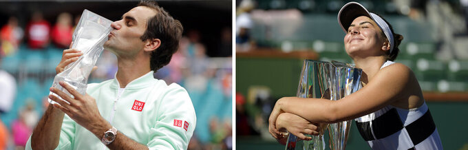 FILE - At left, in a March 31, 2019, file photo, Roger Federer, of Switzerland, kisses the trophy after defeating John Isner in the singles final of the Miami Open tennis tournament in Miami Gardens, Fla. At right, in a March 17, 2019, file photo, Bianca Andreescu, of Canada, smiles as she hugs her trophy after defeating Angelique Kerber, of Germany in the women's final at the BNP Paribas Open tennis tournament in Indian Wells, Calif. Roger Federer raised the prospect of merging the governing bodies that oversee the men's and women's professional tennis tours on Wednesday, April 22, 2020. The 20-time Grand Slam champion began a string of posts on Twitter by saying the shutdown of tennis because of the coronavirus outbreak has given the sport an ideal opportunity to assess its future. (AP Photo/File)