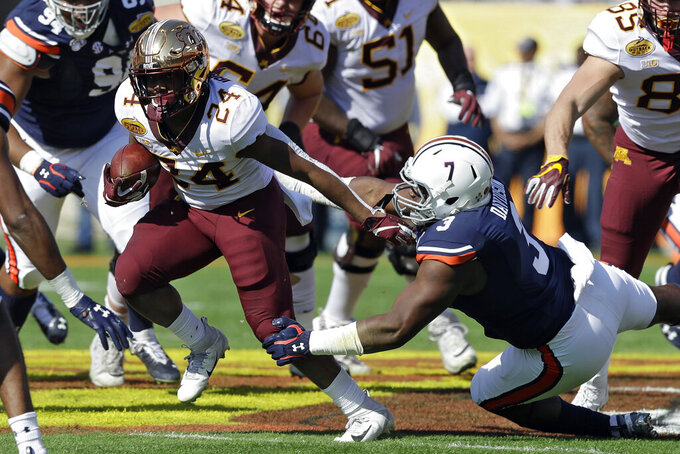 Minnesota running back Mohamed Ibrahim (24) slips a tackle by Auburn defensive end Marlon Davidson (3) during the first half of the Outback Bowl NCAA college football game Wednesday, Jan. 1, 2020, in Tampa, Fla. (AP Photo/Chris O'Meara)