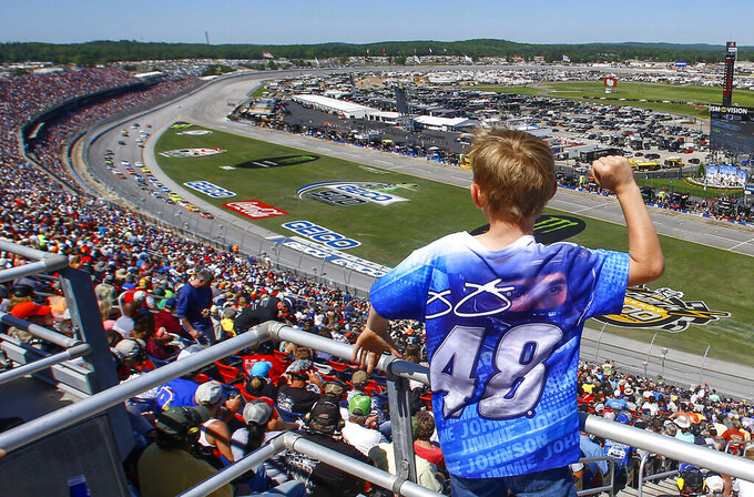 FILE - In this April 29, 2018, file photo, a young fan cheers as racers go by during a NASCAR Talladega auto race at Talladega Superspeedway, in Talladega, Ala. The ever-present air of unpredictability at Talladega Superspeedway is even more pronounced than usual this weekend, with NASCAR having replaced the horsepower-sapping restrictor plates. (AP Photo/Butch Dill, File)