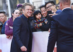 Matt Damon takes a selfie with fans as he attends a premiere for