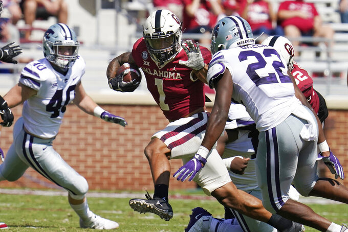 Oklahoma running back Seth McGowan (1) carries between Kansas State defensive end Spencer Trussell (40) and linebacker Daniel Green (22) in the second half of an NCAA college football game Saturday, Sept. 26, 2020, in Norman, Okla. (AP Photo/Sue Ogrocki).
