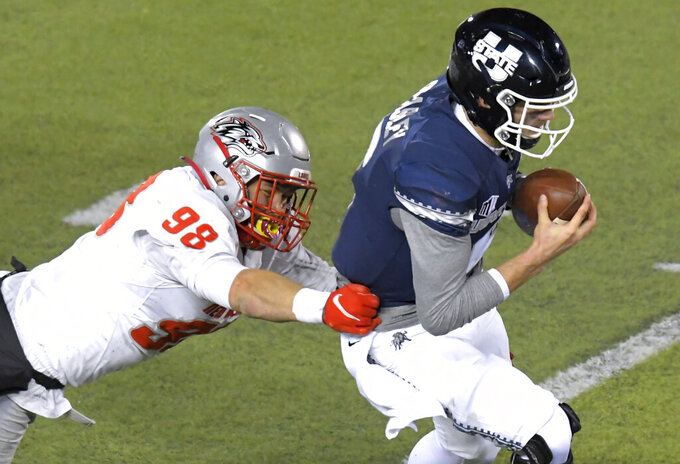 Utah State quarterback Andrew Peasley (6) scrambles away from New Mexico defensive end Joey Noble (98) during the first half of an NCAA college football game Thursday, Nov. 26, 2020, in Logan, Utah. (Eli Lucero/Herald Journal via AP)