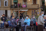 People wearing face masks to protect from coronavirus, sit in a square in Barcelona, Spain, Friday, Oct. 23, 2020. Spain has reported 1 million confirmed infections — the highest number in Western Europe — and at least 34,000 deaths from COVID-19, although experts say the number is much higher since many cases were missed because of testing shortages and other problems. (AP Photo/Emilio Morenatti)
