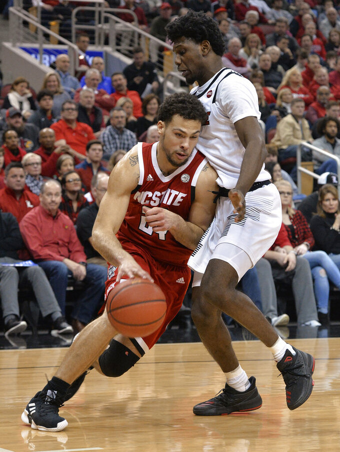 North Carolina State guard Devon Daniels (24) drives against Louisville guard Darius Perry (2) during the first half of an NCAA college basketball game in Louisville, Ky., Thursday, Jan. 24, 2019. (AP Photo/Timothy D. Easley)
