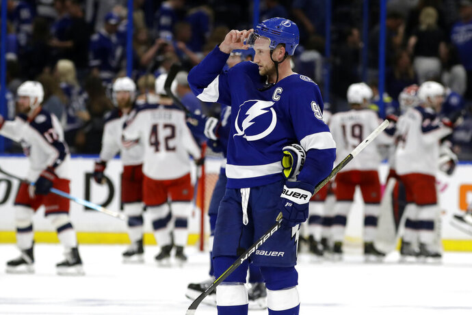 Tampa Bay Lightning center Steven Stamkos (91) skates off as the Columbus Blue Jackets celebrate their 4-3 win during Game 1 of an NHL Eastern Conference first-round hockey playoff series Wednesday, April 10, 2019, in Tampa, Fla. (AP Photo/Chris O'Meara)