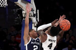 Providence guard Maliek White (4) goes up for a shot against Butler guard Aaron Thompson (2) during the second half of an NCAA college basketball game in the Big East men's tournament Wednesday, March 13, 2019, in New York. Providence won 80-57. (AP Photo/Julio Cortez)
