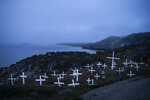 In this Aug. 15, 2019, photo, crosses stand in a cemetery as an iceberg floats in the distance during a foggy morning in Kulusuk, Greenland. Kulusuk's resident Mugu Utuaq says the winter that used to last for as long as 10 months when he was a boy can now be as short as five months. Scientists are hard at work in Greenland, trying to understand the alarmingly rapid melting of the ice. (AP Photo/Felipe Dana)