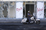 A motorcycle police officer passes by broken glass doors of a shop in the aftermath of a protest against the Lebanese government in Beirut, Lebanon, Saturday, Oct. 19, 2019. The blaze of protests was unleashed a day earlier when the government announced a slate of new proposed taxes, including a $6 monthly fee for using Whatsapp voice calls. Arabic on the wall reads