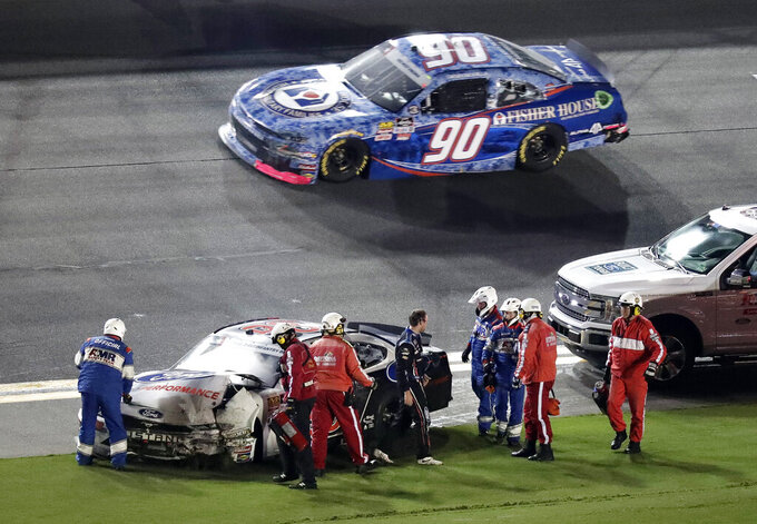 Chase Briscoe, center, is helped from his car by track personnel and rescue workers after he was involved in a crash during a NASCAR Xfinity Series auto race at Daytona International Speedway, Friday, July 5, 2019, in Daytona Beach, Fla. (AP Photo/John Raoux)
