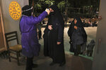 A worshipper has her temperature checked to help prevent the spread of the coronavirus as she enters the Tehran University mosque to pray on Laylat al-Qadr, or the night of destiny, during holy fasting month of Ramadan, in Tehran, Iran, Tuesday, May 12, 2020. On Tuesday authorities allowed mosques temporarily reopen for limited hours up to two hours strictly observing health and social procedures to prevent spreading the disease, in the predominantly Shiite country for three continuous nights from Tuesday which people believe the Laylat al-Qadr night happens either on 19th, 21st or 23rd of the holy month of Ramadan. Laylat al-Qadr is the night when Muslims believe the Quran was first revealed to prophet Muhammad. (AP Photo/Vahid Salemi)