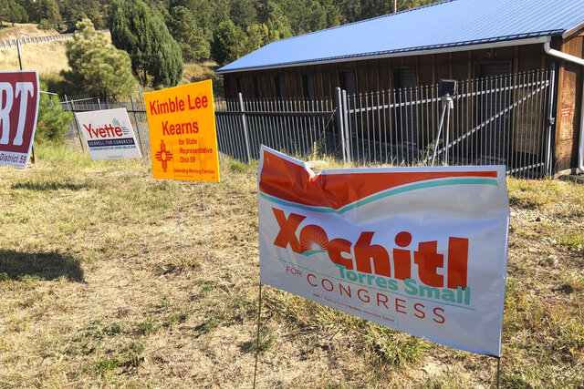 A damaged campaign sign for Democratic U.S. Rep. Xochitl Torres Small sits in front of the Wild West Ski Shop in Ruidoso, N.M., on Oct. 6, 2020. New Mexico is on the verge of electing the nation's largest all-female of color U.S. House delegation but the close race in the state's southern district, where Ruidoso sits, is grabbing the most attention. (AP Photo/ Russell Contreras)