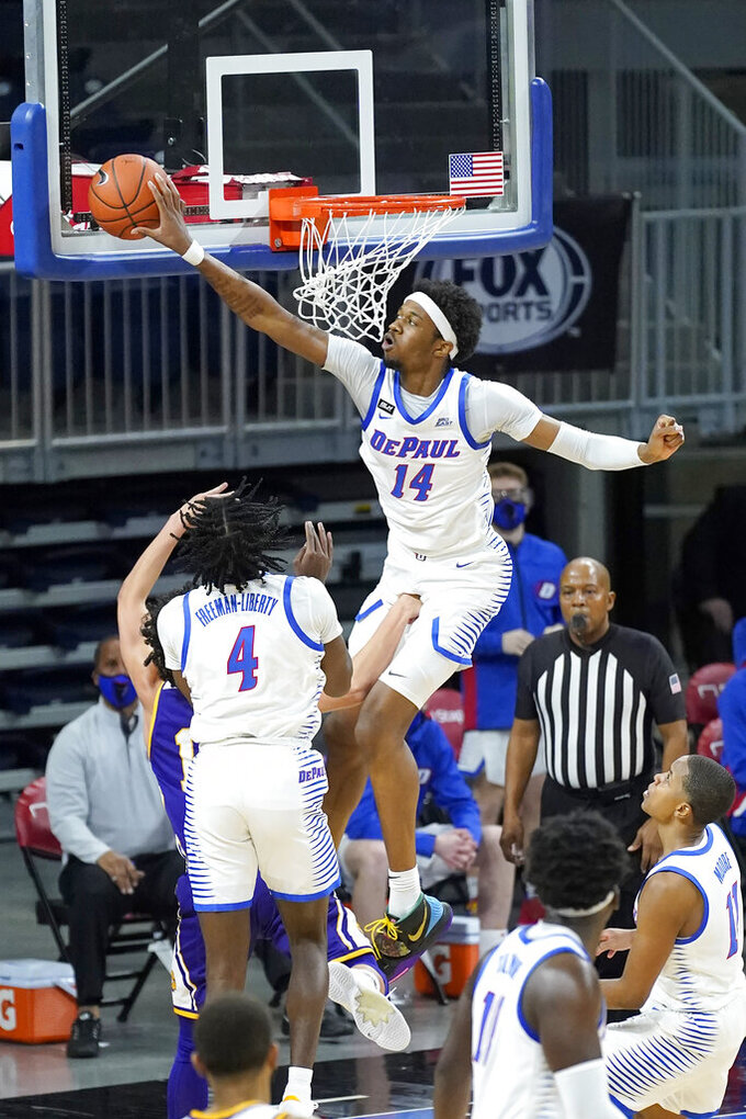 DePaul's Nick Ongenda (14) blocks the shot of Western Illinois' JJ Flores as Javon Freeman-Liberty (4) watches during the first half of an NCAA college basketball game Wednesday, Dec. 23, 2020, in Chicago. (AP Photo/Charles Rex Arbogast)
