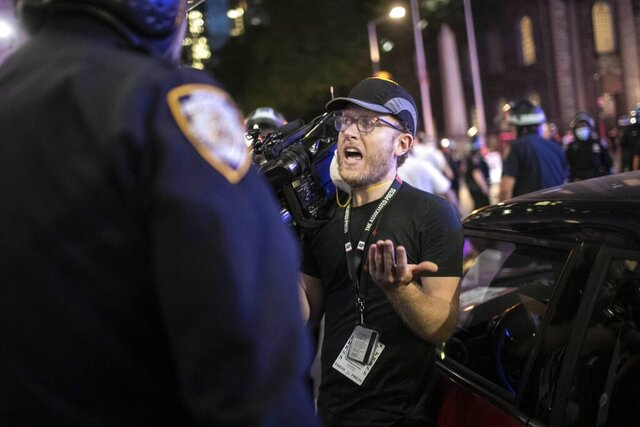 "Associated Press videojournalist Robert Bumsted reminds a police officer that the press are considered ""essential workers"