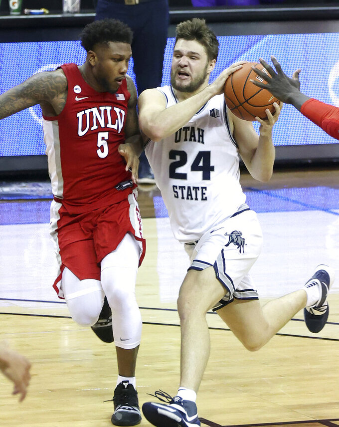 Utah State guard Rollie Worster (24) drives as UNLV guard David Jenkins Jr. (5) defends during the second half of an NCAA college basketball game in the quarterfinals of the Mountain West Conference men's tournament Thursday, March 11, 2021, in Las Vegas. (AP Photo/Isaac Brekken)