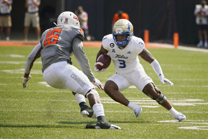 Tulsa running back Shamari Brooks (3) is defended by Oklahoma State linebacker Devin Harper (16) in the first half of an NCAA college football game, Saturday, Sept. 11, 2021, in Stillwater, Okla. (AP Photo/Sue Ogrocki)