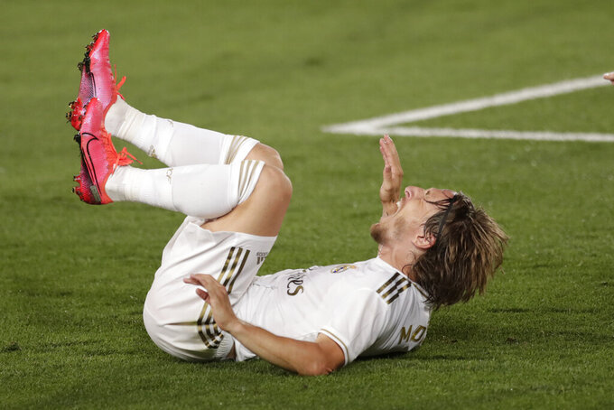 Real Madrid's Luka Modric, reacts after stopped during the Spanish La Liga soccer match between Real Madrid and Deportivo Alaves at the Alfredo di Stefano stadium in Madrid, Spain, Friday, July 10, 2020. (AP Photo/Bernat Armangue)