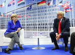 FILE - In this July 11, 2018 file photo, President Donald Trump and German Chancellor Angela Merkel sit, during their bilateral meeting at NATO headquarters in Brussels, Belgium. NATO Secretary-General Jens Stoltenberg is playing down differences among member countries as the military alliance marks its 70th anniversary in Washington on April 4, 2019. (AP Photo/Pablo Martinez Monsivais, File)