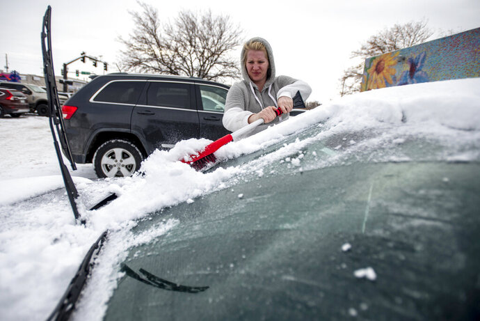 Brittany Culp brushes snow off of her windshield on a windy and snowy morning in Greeley, Colo., Saturday, Nov. 30, 2019. The weather caused the city to cancel its annual Greeley Lights the Night parade, which was scheduled in the evening. (Alex McIntyre/The Greeley Tribune via AP)