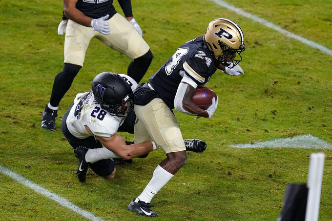 Purdue wide receiver Alex Maxwell (24) is tacked by Northwestern linebacker Chris Bergin (28) on a kickoff return during the first half of an NCAA college football game in West Lafayette, Ind., Saturday, Nov. 14, 2020. (AP Photo/Michael Conroy)