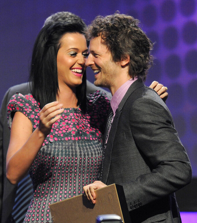 """FILE - This April 21, 2010 file photo shows recording artist Katy Perry, left, on stage with Lukasz """"Dr. Luke"""" Gottwald as he accepts the Songwriter of the Year award at the 27th Annual ASCAP Pop Music Awards in Los Angeles. Luke is marking a comeback with the funky Doja Cat hit """"Say So,"""" which topped this week's Billboard Hot 100 chart thanks to its remix featuring rap queen Nicki Minaj. (AP Photo/Chris Pizzello, File)"""