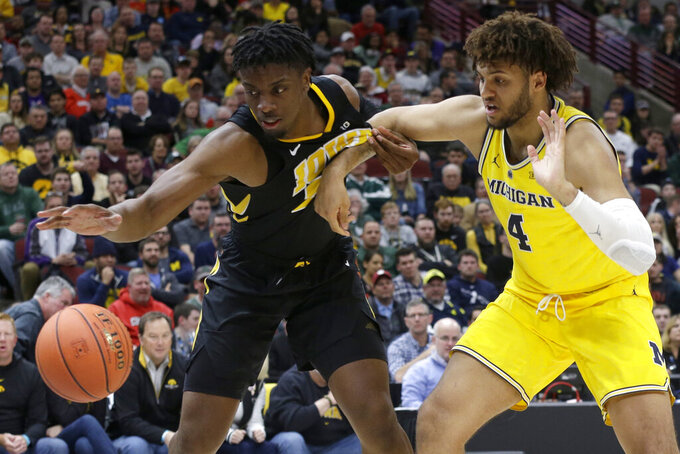Iowa's Tyler Cook (25) and Michigan's Isaiah Livers (4) battle for a loose ball during the second half of an NCAA college basketball game in the quarterfinals of the Big Ten Conference tournament, Friday, March 15, 2019, in Chicago. (AP Photo/Kiichiro Sato)