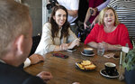 New Zealand Prime Minister Jacinda Ardern, left, and Megan Woods talk with colleagues at a cafe in Auckland, New Zealand, Sunday, Oct. 18, 2020. Ardern has won a second term in office in an election landslide of historic proportions. (AP Photo/Mark Baker)
