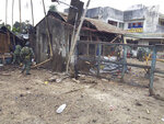 In this Friday, June 28, 2019 photo, Philippine troops examine the scene of the suicide attack carried out by Muslim militants at a military camp in Indanan township, on the island of Jolo in Sulu province that killed five people and the bombers in the southern Philippines. Maj. Gen. Cirilito Sobejana told The Associated Press Tuesday, July 2, 2019, that the family of the 23-year-old militant, Norman Lasuca, has identified him as one of the bombers who detonated a bomb on Friday at the gate of an army encampment in Sulu province's Indanan town. Lasuca is the first known Filipino militant to have agreed to carry out a suicide bombing, a development that has concerned Philippine security officials. (AP Photo)