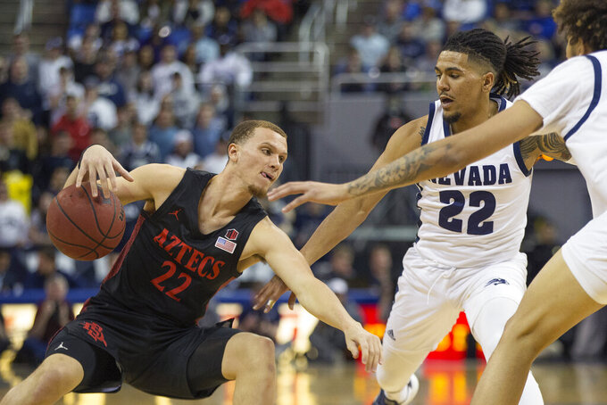 San Diego State guard Malachi Flynn (22) slips as he drives past Nevada guard Jazz Johnson (22) during the first half of an NCAA college basketball game played at Lawlor Events Center in Reno, Nev., Saturday, Feb. 29, 2020. (AP Photo/Tom R. Smedes)