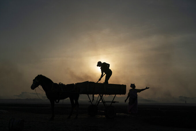A woman gestures as a man unloads his horse-drawn cart of the catch brought by fishermen at Bargny beach, some 35 kilometers (22 miles) east of Dakar, Senegal, Thursday April 22, 2021. (AP Photo/Leo Correa)