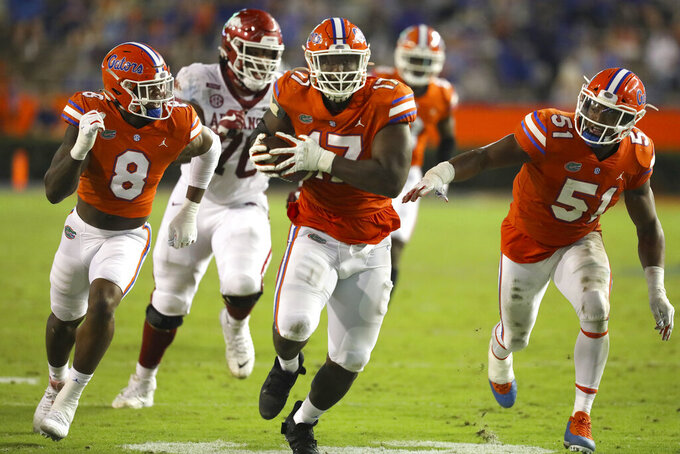 Florida defensive lineman Zachary Carter (17) runs for a touchdown after picking up an Arkansas fumble during an NCAA college football game in Gainesville, Fla., Saturday, Nov. 14, 2020. (Brad McClenny/The Gainesville Sun via AP)