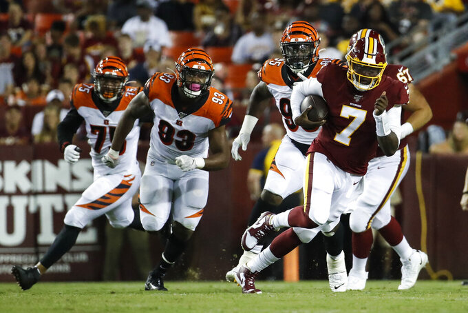 Washington Redskins quarterback Dwayne Haskins (7) scrambles away from Cincinnati Bengals defensive end Jordan Willis (75), defensive tackle Andrew Brown (93) and defensive tackle Renell Wren (95) during the first half of an NFL preseason football game Thursday, Aug. 15, 2019, in Landover, Md. (AP Photo/Alex Brandon)
