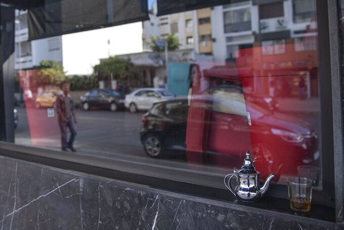 FILE - In this Monday, March 16, 2020 file photo, a glass of Moroccan tea is left by a window of a closed down coffee shop, after the Moroccan government announced further restrictions to avoid the spread of coronavirus, including closure of cafes and mosques, in the capital Rabat, Morocco. Morocco has imposed a curfew, closed restaurants in major cities and banned public and private gatherings for three weeks — including the usually festive New Year's Eve — to curb the spread of the virus.The curfew between 9 p.m and 6 a.m went into effect Wednesday, Dec. 23, 2020 and is set to last until Jan. 13.  (AP Photo/Mosa'ab Elshamy, File)