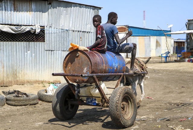 In this photo taken Sunday, Sept. 30, 2018, two South Sudanese boys ride a donkey cart in Paloch, South Sudan. The oil industry in South Sudan has left a landscape pocked with hundreds of open waste pits with the water and soil contaminated with toxic chemicals and heavy metals, and accounts of